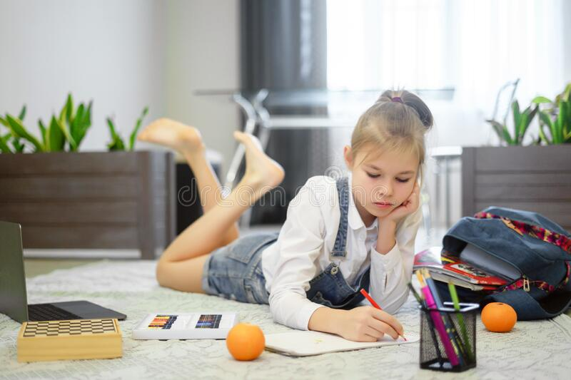 Cute little girl is drawing on a floor in living room royalty free stock photography