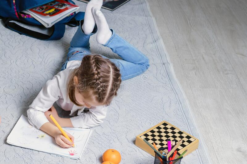 Cute little girl is drawing on a floor in living room stock photography