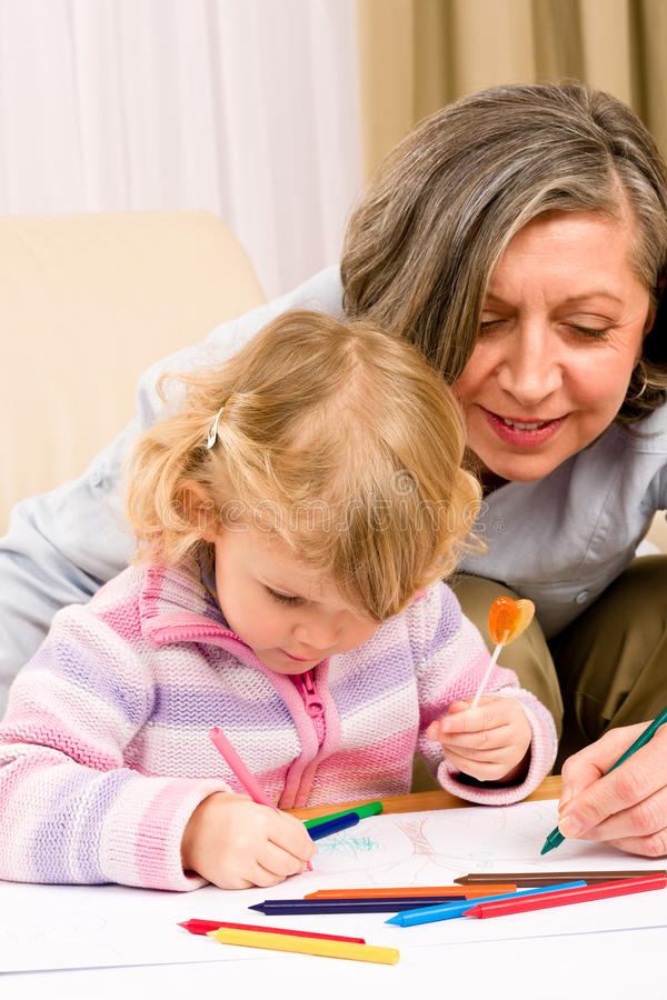 Download Cute Little Girl Drawing With Grandmother At Home Stock Image - Image: 23024077