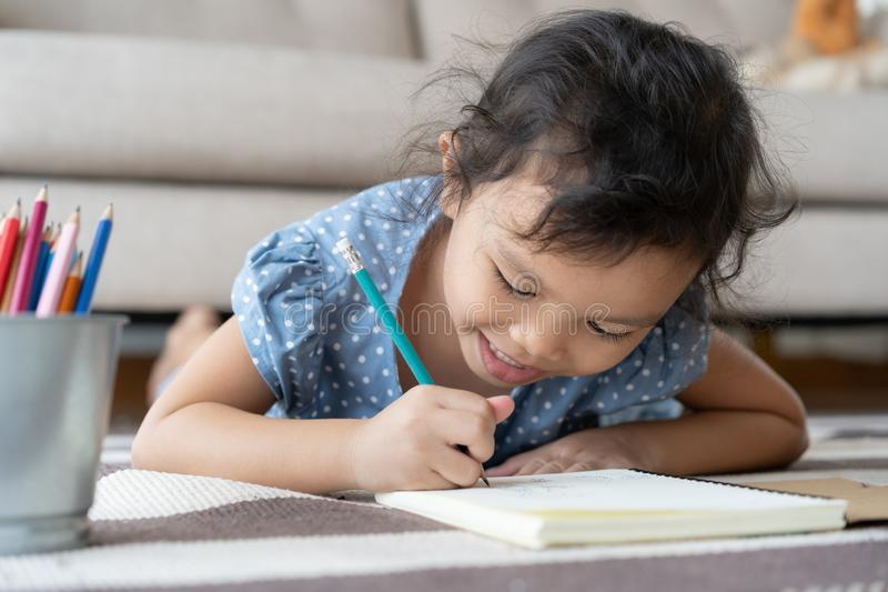 Cute little girl drawing homework and writing with pen on paper in her home royalty free stock photo