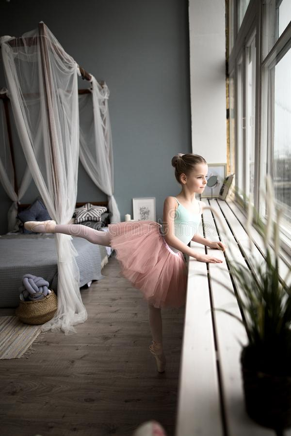 Little girl dreams of becoming a ballerina. Child in a pink tutu dancing in a kids room. Cute little girl dreams of becoming a ballerina. Child in a pink tutu royalty free stock photography