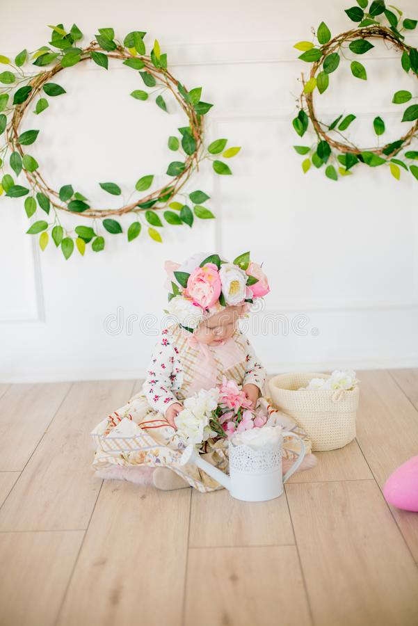 Cute little girl in a dress with a flower print and a hat with flowers in the Easter decorations in the studio. Little girl with easter eggs and flowers in a stock photos