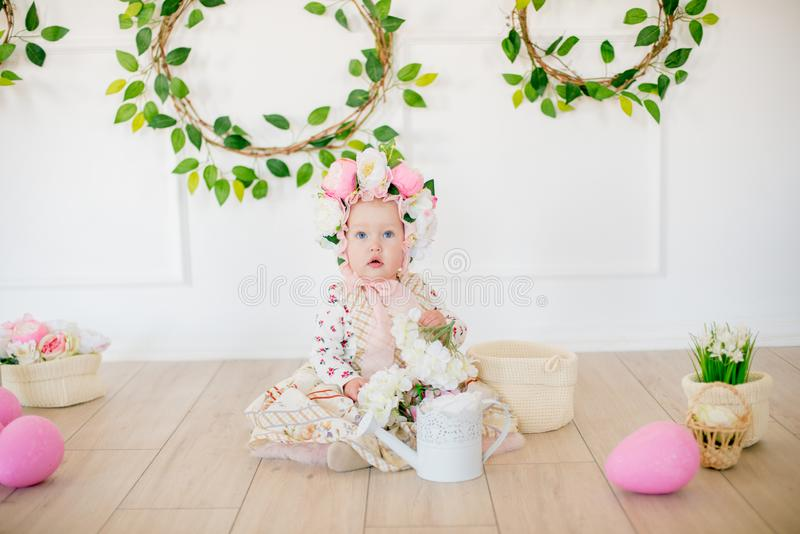 Cute little girl in a dress with a flower print and a hat with flowers in the Easter decorations in the studio. Little girl with easter eggs and flowers in a stock images
