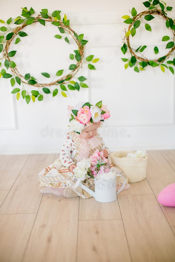 Cute little girl in a dress with a flower print and a hat with flowers in the Easter decorations in the studio. Little girl with easter eggs and flowers in a stock photo