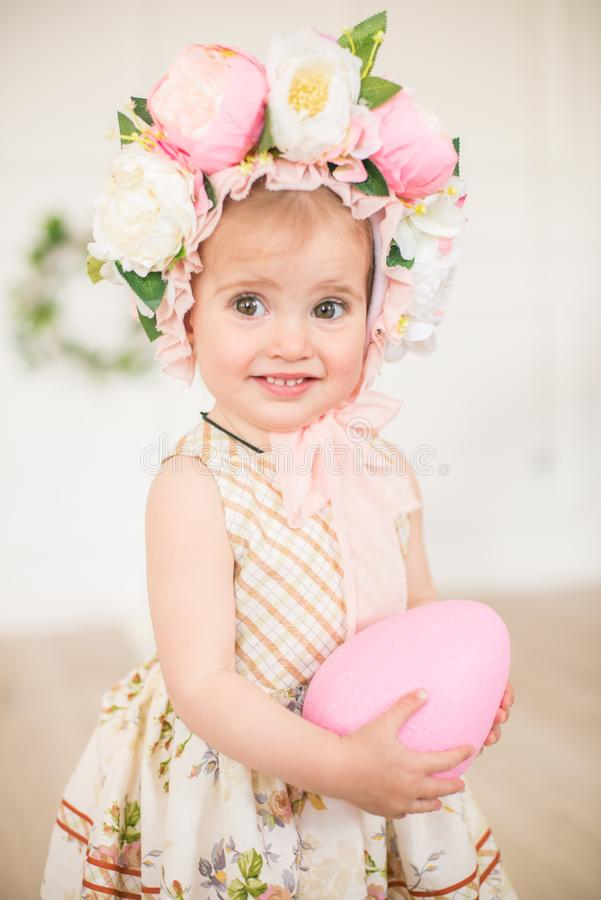 Cute little girl in a dress with a flower print and a hat with flowers in the Easter decorations in the studio. Little girl with easter eggs and flowers in a royalty free stock photography