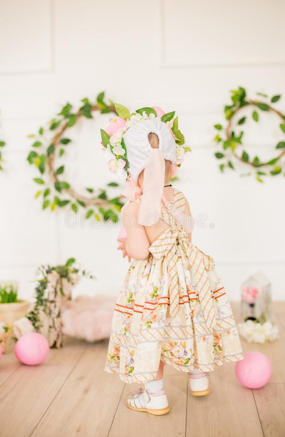 Cute little girl in a dress with a flower print and a hat with flowers in the Easter decorations in the studio. Little girl with easter eggs and flowers in a royalty free stock image