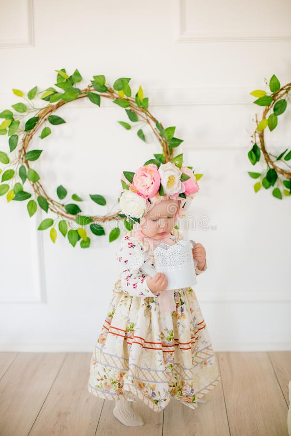Cute little girl in a dress with a flower print and a hat with flowers in the Easter decorations in the studio. Little girl with easter eggs and flowers in a royalty free stock photos