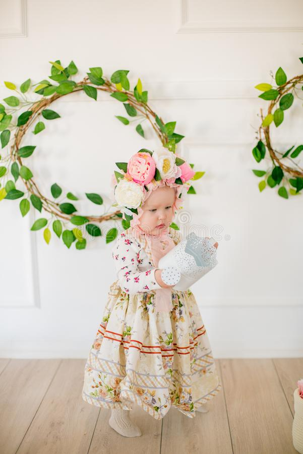 Cute little girl in a dress with a flower print and a hat with flowers in the Easter decorations in the studio. Little girl with easter eggs and flowers in a stock image