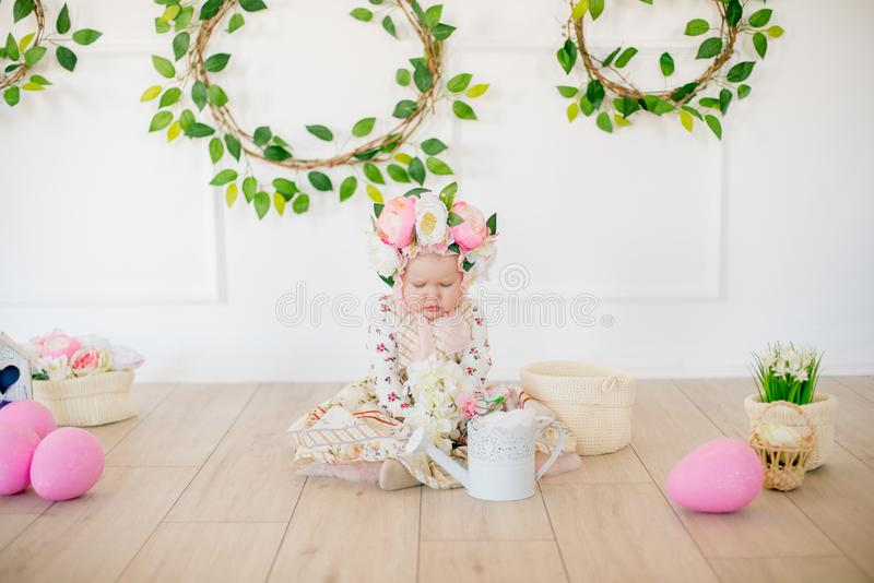 Cute little girl in a dress with a flower print and a hat with flowers in the Easter decorations in the studio. Little girl with easter eggs and flowers in a royalty free stock photo