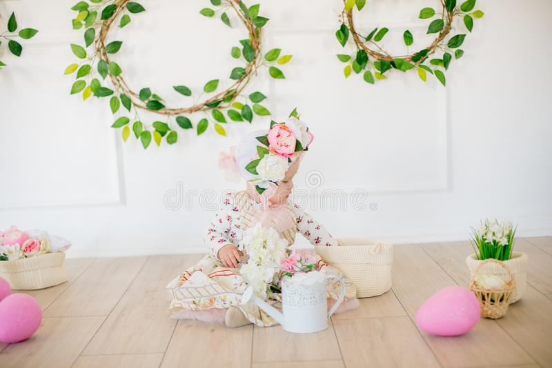 Cute little girl in a dress with a flower print and a hat with flowers in the Easter decorations in the studio. Little girl with easter eggs and flowers in a stock photography