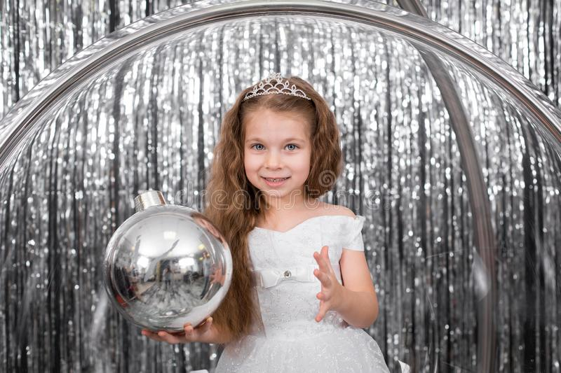 Cute little girl dress posing standing in a large glass ball chair. Holding a large silver ball for decorating a Christmas tree royalty free stock photo