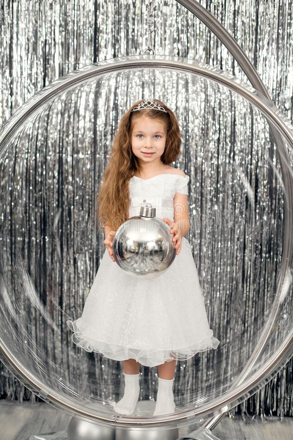Cute little girl dress posing standing in a large glass ball chair. Holding a large silver ball for decorating a Christmas tree stock images
