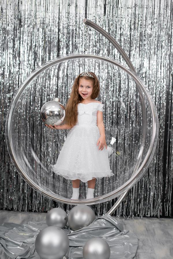 Cute little girl dress posing standing in a large glass ball chair. Holding a large silver ball for decorating a Christmas tree royalty free stock images