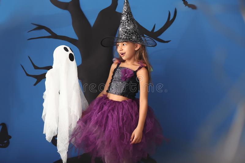 Cute little girl dressed as witch for Halloween and funny ghost against color wall with creepy decor royalty free stock photo