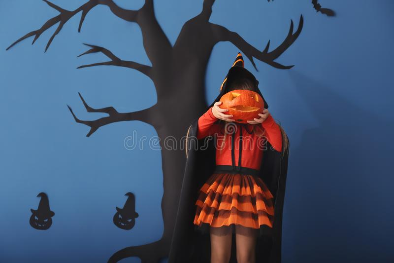 Cute little girl dressed as witch for Halloween and with Jack-o-lantern standing against color wall with creepy decor royalty free stock images