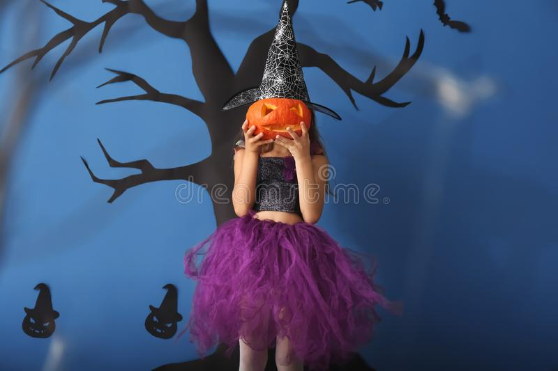 Cute little girl dressed as witch for Halloween and with Jack-o-lantern standing against color wall with creepy decor stock images