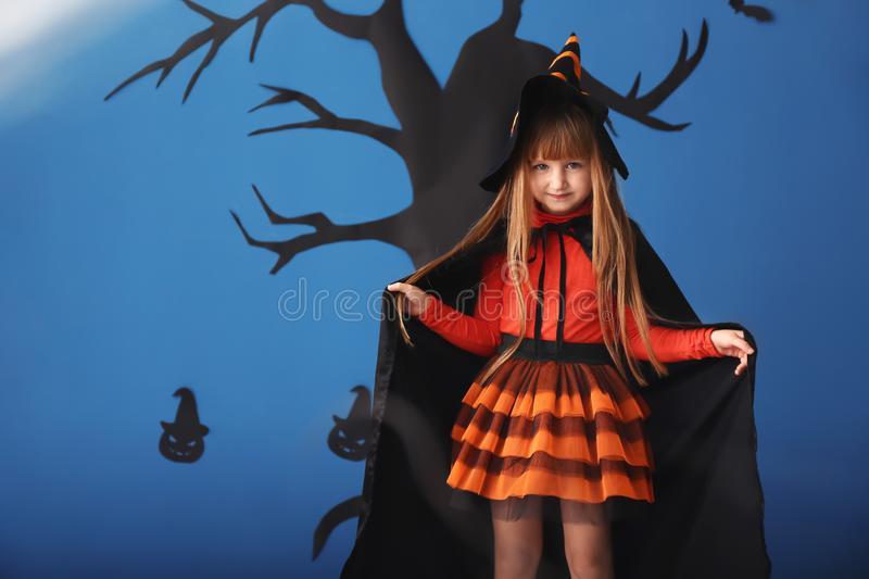 Cute little girl dressed as witch for Halloween standing against color wall with creepy decor royalty free stock photography
