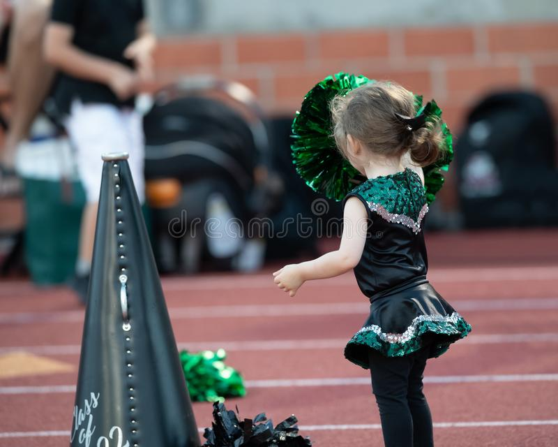 Cute little girl dressed in a cheerleader costume at a football game royalty free stock photography