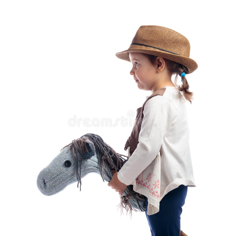 Cute little girl dressed like a cowboy playing with a homemade h stock image