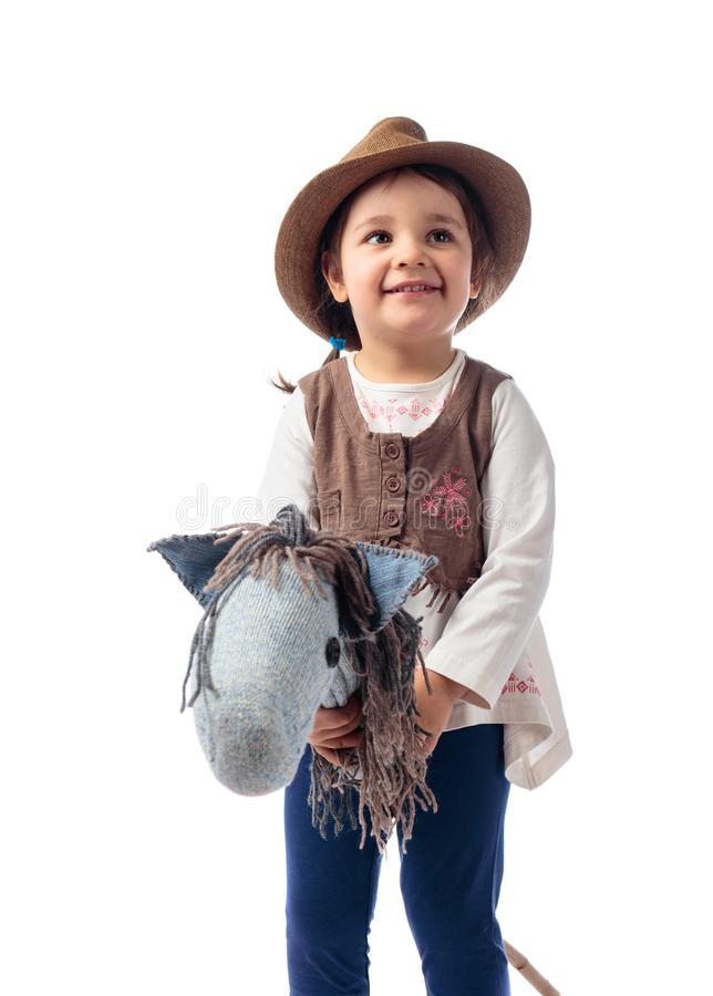 Cute little girl dressed like a cowboy playing with a homemade h royalty free stock images