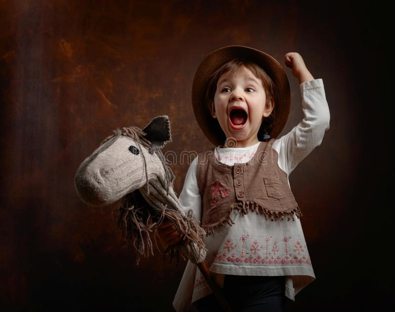 Cute little girl dressed like a cowboy playing with a homemade h royalty free stock photography