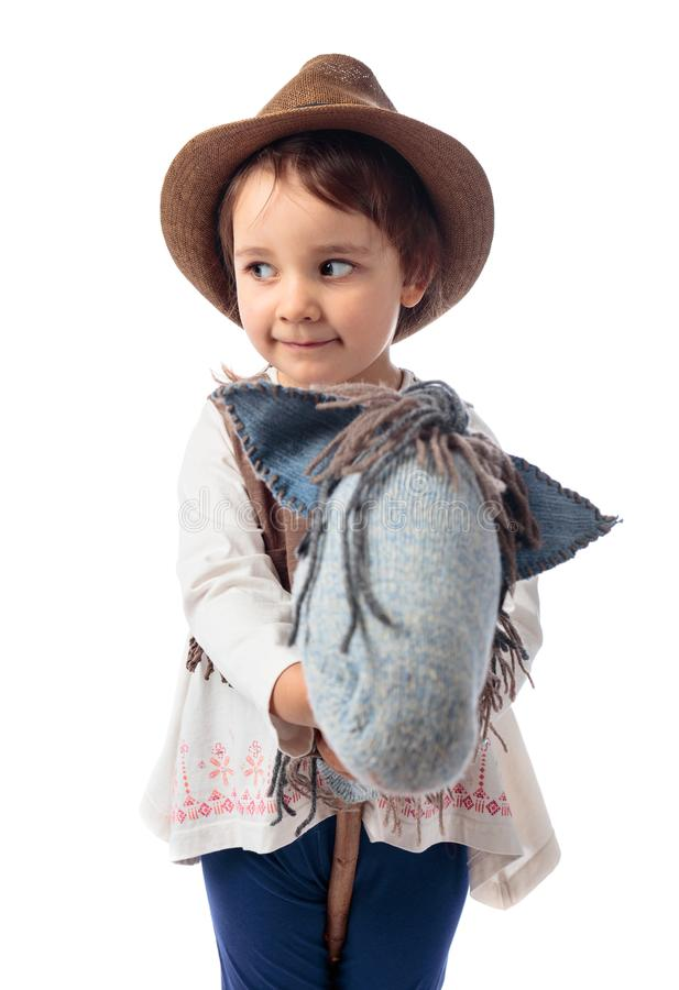 Cute little girl dressed like a cowboy playing with a homemade h royalty free stock image