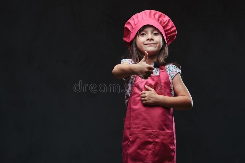 Cute little girl dressed in pink cook posing with thumbs up in a studio. Isolated on a dark textured background. royalty free stock image