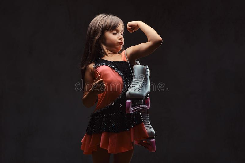 Cute little girl dressed in skater dress holds ice skates and shows muscles. Isolated on dark textured background. stock images