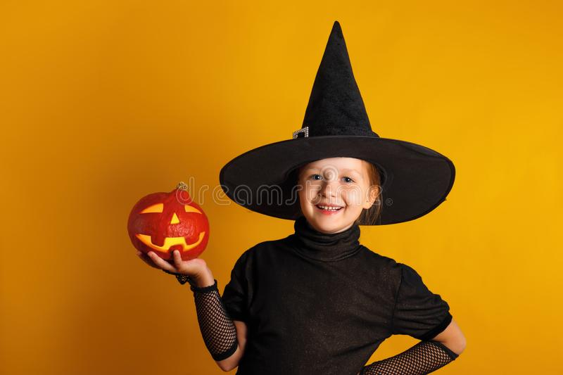 Cute little girl dressed in a witch costume holds a pumpkin jack lantern on a yellow background. Halloween celebration royalty free stock image