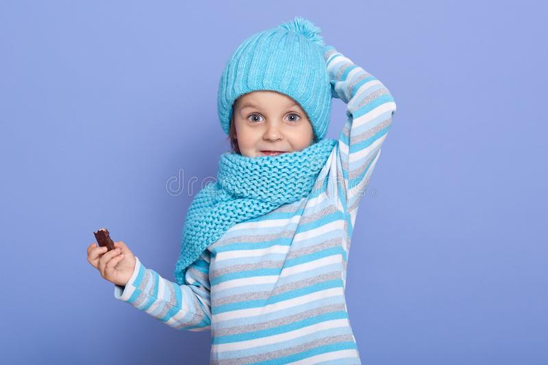 Cute little girl dresses striped casual shirt, warm hat with pom pom and scarf, keeping hand on her cap, holding candy in hansd, royalty free stock image