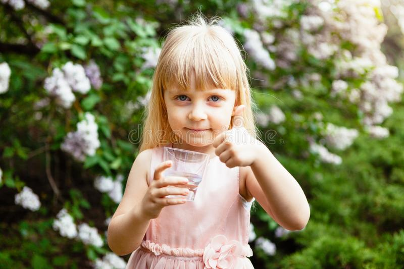 Cute little girl drink glass of water and show thumb up outdoors in summer royalty free stock photography