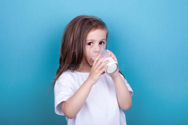 Cute little girl drinking milk from glass stock image