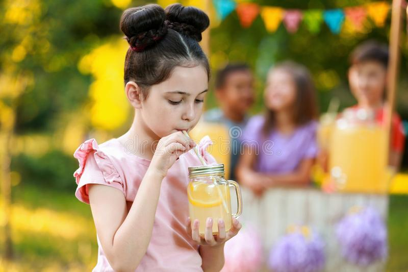 Cute little girl drinking natural lemonade in park. Summer refreshing beverage stock photos