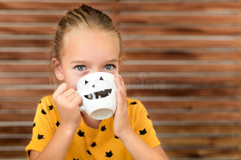 Cute little girl drinking pumpkin soup out of a cup with Halloween anthropomorphic smiley face. Autumn season comfort food. Cute little girl drinking pumpkin stock image