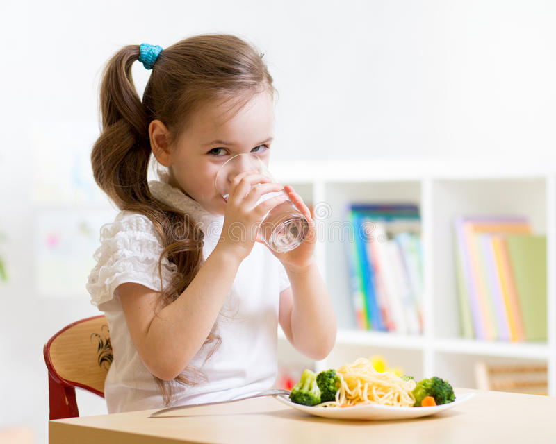 Cute little girl drinking water stock images