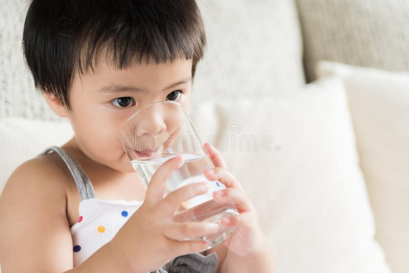 Cute little girl drinking water on sofa at home. stock photo