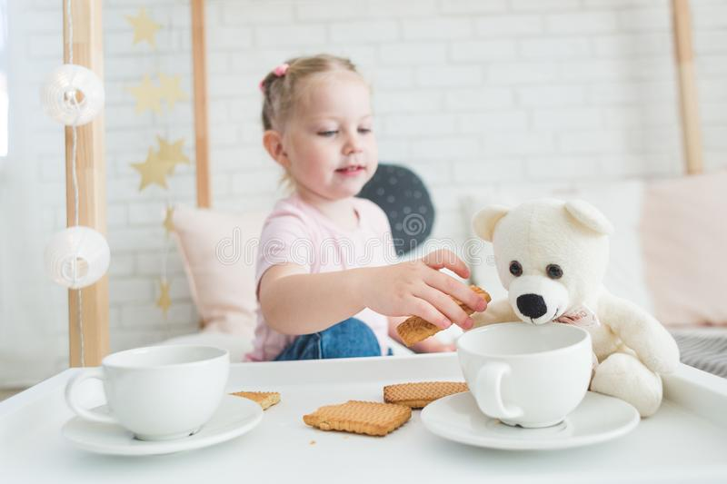Cute little girl drinks tea with her teddy bear. stock images