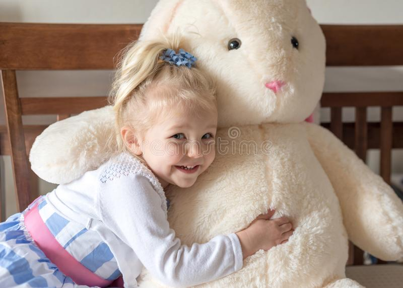 Cute little girl in Easter dress hugging stuffed bunny. Smiling little girl hugging big stuffed bunny on Easter royalty free stock photo