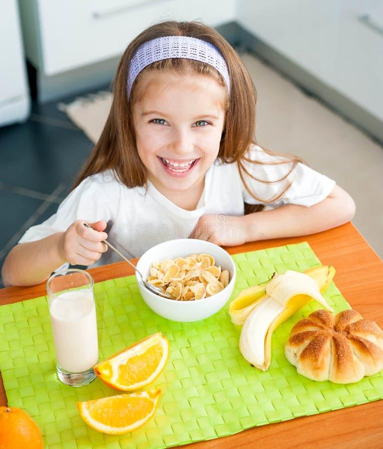 Little girl eating her breakfast stock images