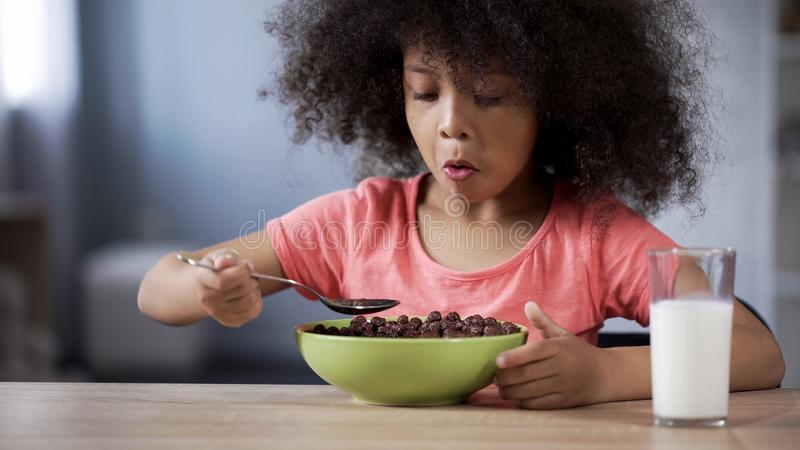 Cute little girl eating chocolate cornflakes for breakfast, risk of diabetes royalty free stock photos