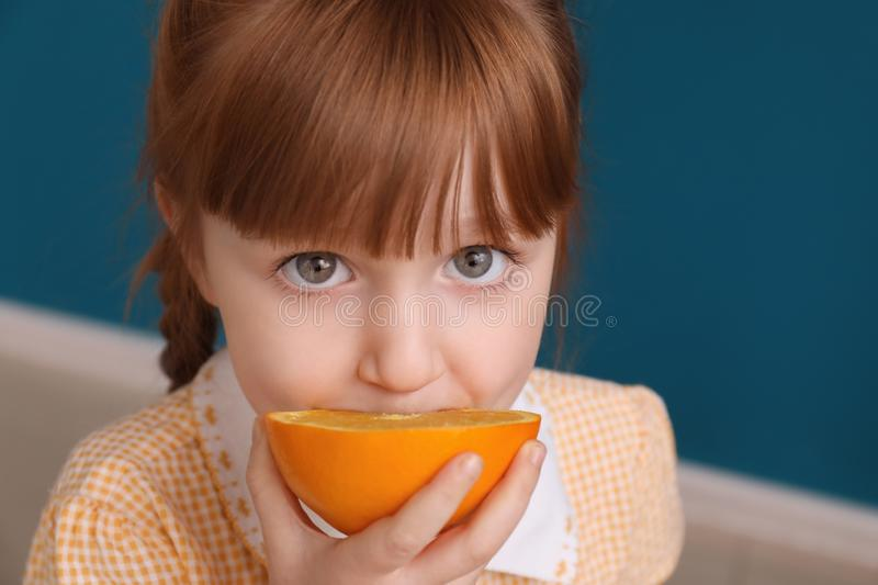 Cute little girl eating citrus fruit at home, closeup stock photography