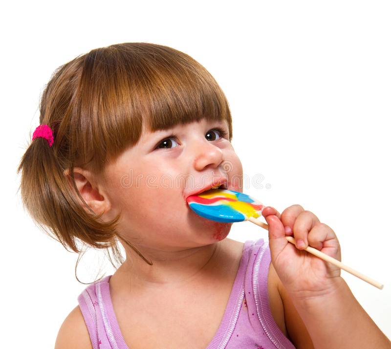 Cute little girl eating a colored lollipop. A Cute little girl eating a colored lollipop royalty free stock photos