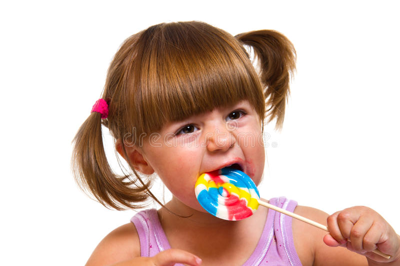 Cute little girl eating a colored lollipop. A Cute little girl eating a colored lollipop royalty free stock photography