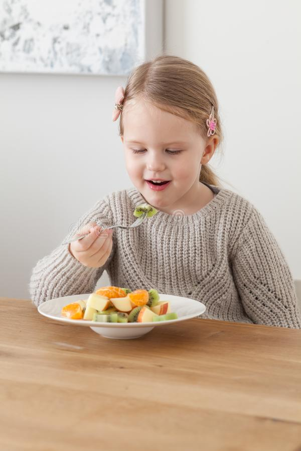 Cute little girl eating a fruit salad in design dining room. Child having a dinner at home. Healthy nutrition for small royalty free stock images