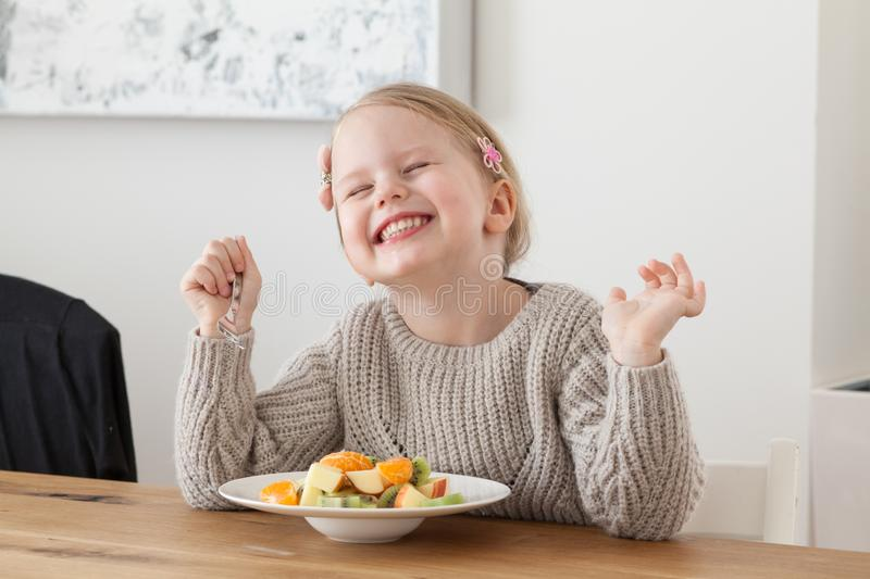 Cute little girl eating a fruit salad in design dining room. Child having a dinner at home. Healthy nutrition for small royalty free stock image