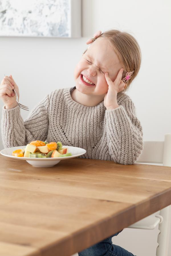Cute little girl eating a fruit salad in design dining room. Child having a dinner at home. Healthy nutrition for small royalty free stock photography