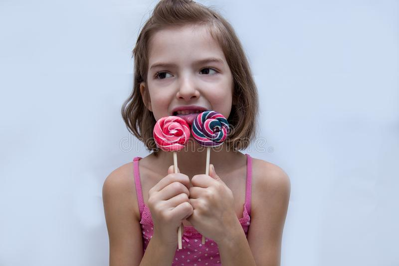 Beautiful cute little girl eating lollipop royalty free stock photography