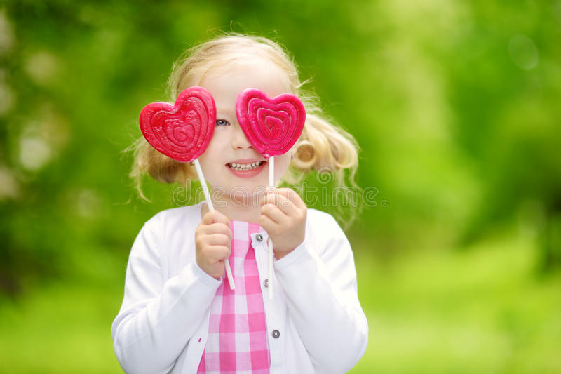 Cute little girl eating huge heart-shaped lollipop outdoors on beautiful summer day royalty free stock photography