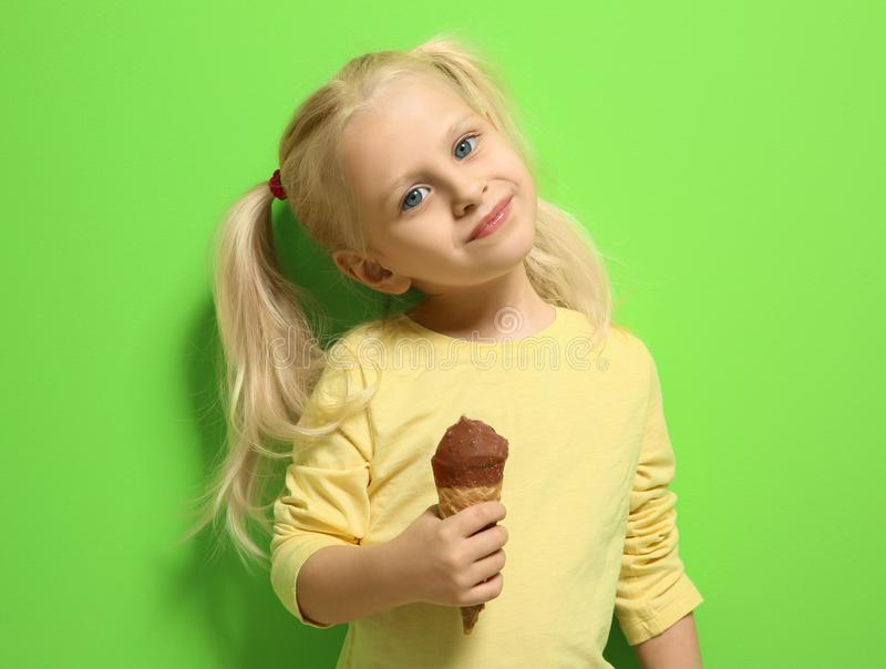 Cute little girl eating ice cream on color background stock photos