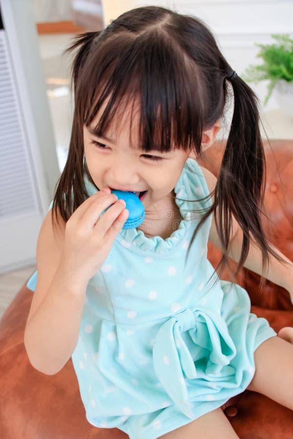 Cute little girl eating macaron. royalty free stock photo